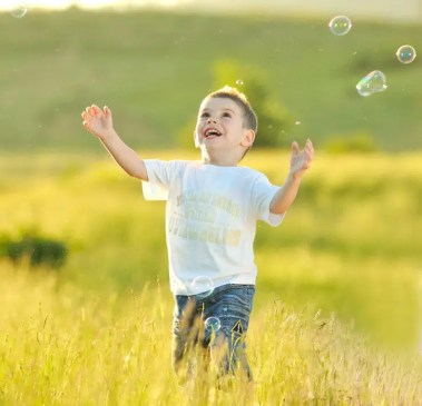 child chasing bubbles in field