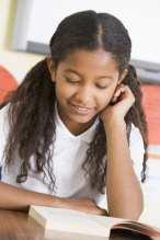 Schoolgirl reading a book in class