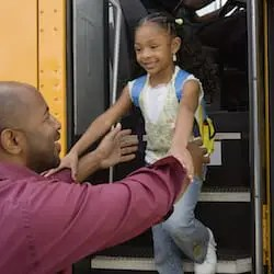 Mature man picking up his little daughter from school bus
