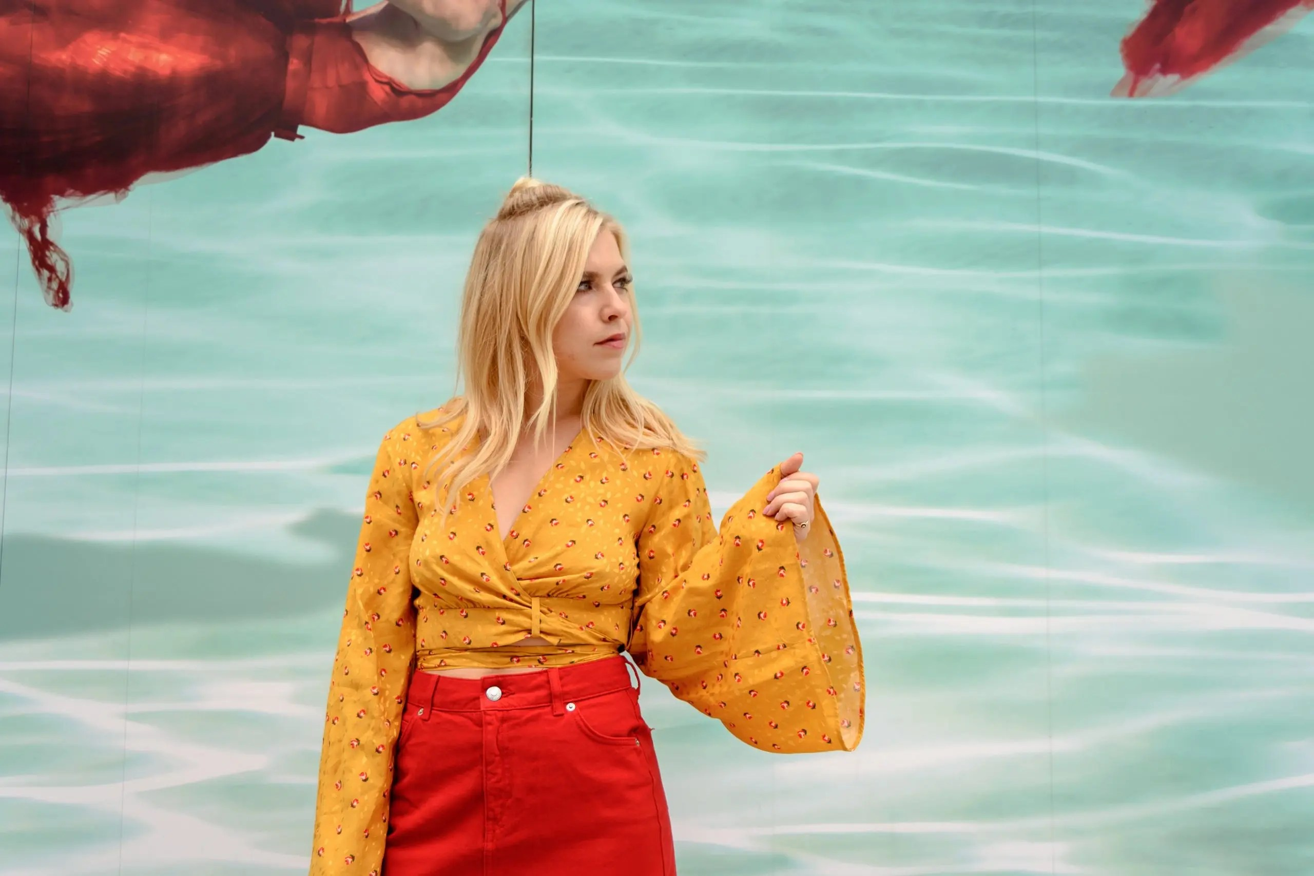 Model standing in front of an aqua green background contrasting a yellow blouse and red jeans.