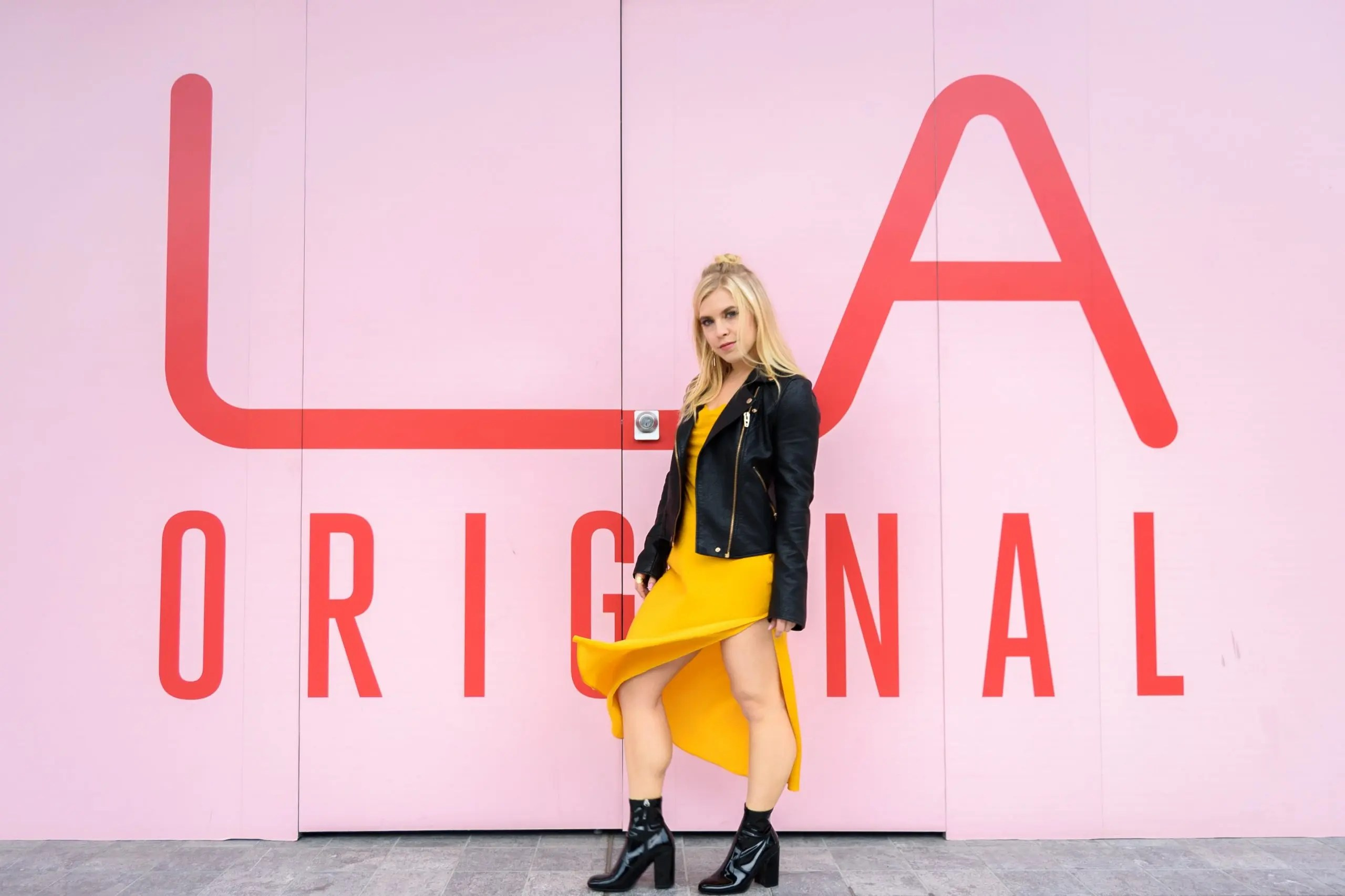 """Model standing in front of a sign """"LA Original"""" that is shaded in pink contrasting with her black jacket and yellow dress."""
