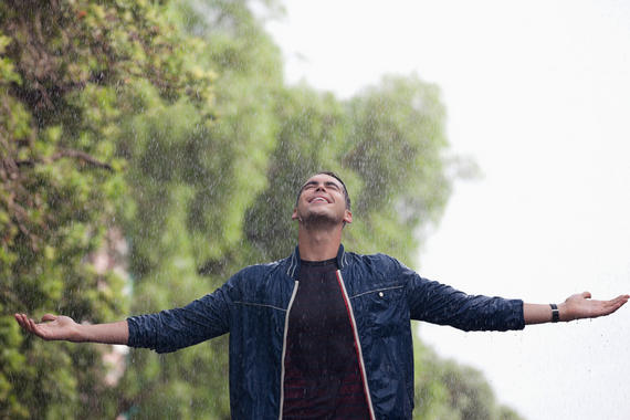 Man with arms outstretched in rain