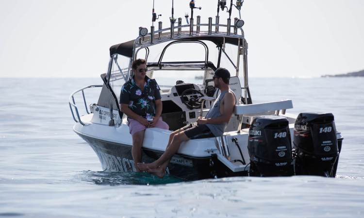 Two men sitting on the gunnels of the Edencraft 6.0m Offshore boat as they relax in the sun