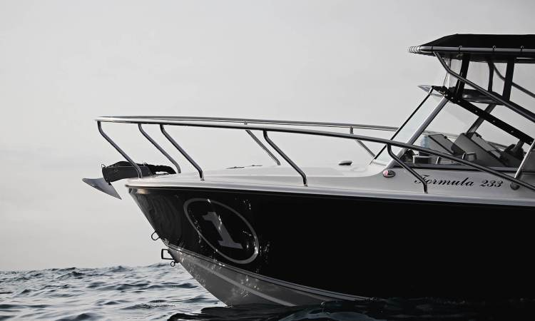 Edencraft 233 Formula Classic with windscreen, bimini & clears at rest on the water