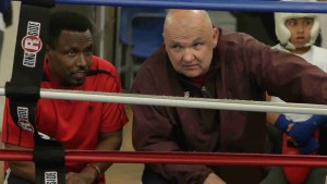 Boxing coach watches outside ring