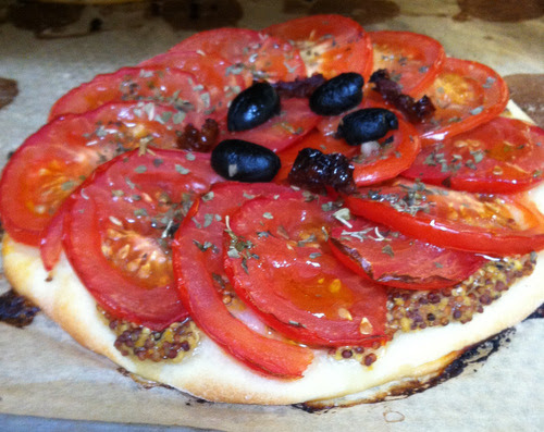 Tarte fine: a pastry base, topped with mustard and sliced tomato