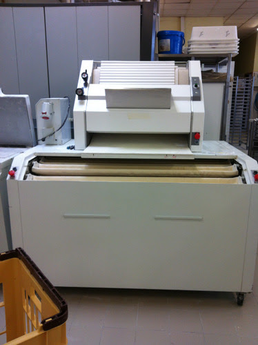 This is the shaping machine. It's hard to get a sense of scale, but it's about 2 metres across. Once the dough is divided, you place the pieces of dough, four or 5 at a time into the troughs (cream coloured). There are 32 of these in all, you rotate them as you fill each one. You then place the dough in the silver hopper and out pops a shaped baguette.