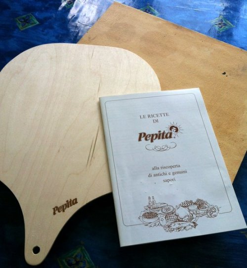 The Pepita Fireclay plate comes with a wooden paddle and recipe book (in English)
