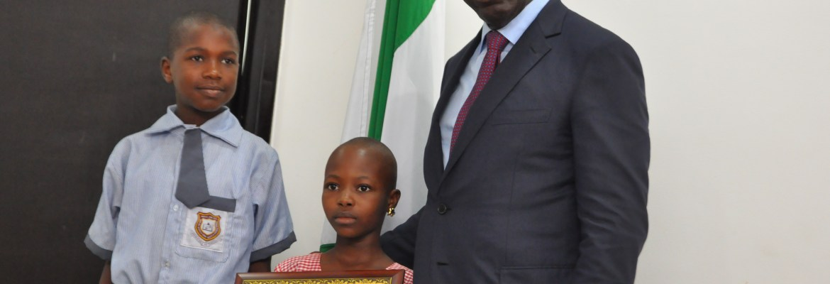 Edo State Governor, Mr. Godwin Obaseki (right) pose with Master Yusuf Hassan of Eson Nerie Primary School (left) and Miss Faith Toun-Agbai of Eguare Primary School, when they visited the governor after winning the South-South region of Lafarge National Literacy competition, in Government House, Edo State. Attachments area