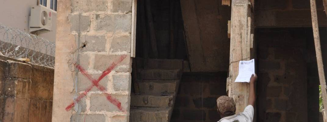 Officials of the Ministry of Physical Planning and Urban Development,  marking a building which contravened Edo state's laws on urban development, in Benin City,  the state capital. The building is being marked for demolition after final notice was issued to the developer.