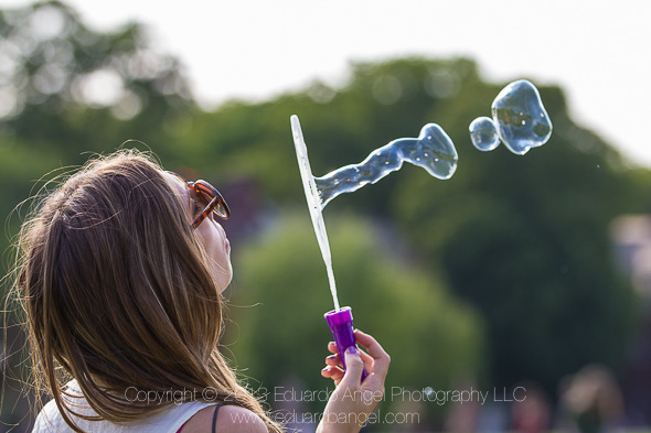 Young girl plays with soap bubbles in New York City during the summer.