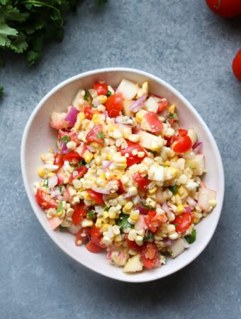 Summer corn salad with stone fruit and feta, in an off-white bowl, on a gray background.