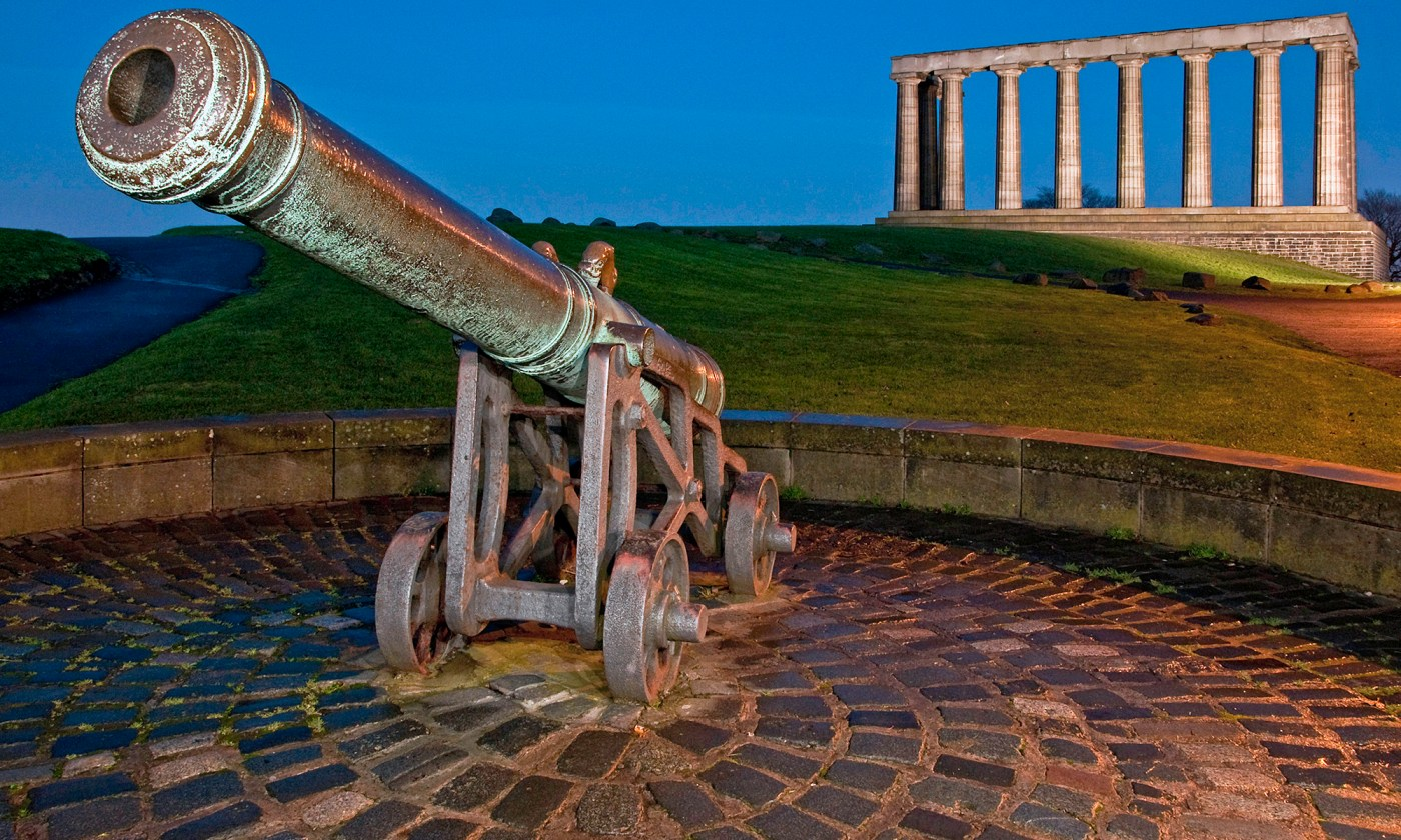 Cannon with National Monument at Night