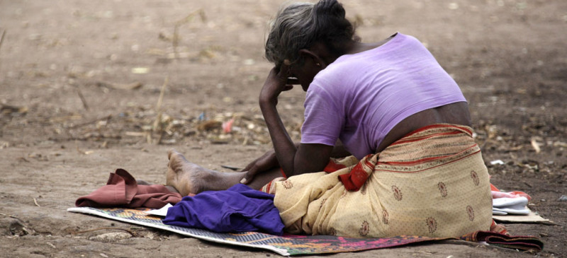 A Tamil woman sits on the ground in the Manik Farm refugee camp located on the outskirts of northern Sri Lankan town of Vavuniya May 26, 2009. U.N. Secretary-General Ban Ki-moon toured Sri Lanka's largest war displaced persons camp on Saturday during a trip to press for wider humanitarian access and political reconciliation. REUTERS/David Gray (SRI LANKA MILITARY CONFLICT POLITICS SOCIETY)