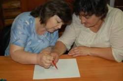Une aide-enseignante et un enseignant du système classique dessinent ensemble avec un seul crayon. Le but de l'activité est de provoquer l'autoréflexion sur le travail d'équipe, montrer et suivre un exemple.