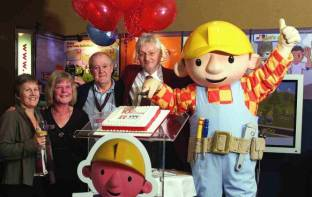 Susie Miles from EENET and the founders of Inclusive Technology celebrate 10 years. (Children's TV character, Bob the Builder, is cutting the birthday cake!)