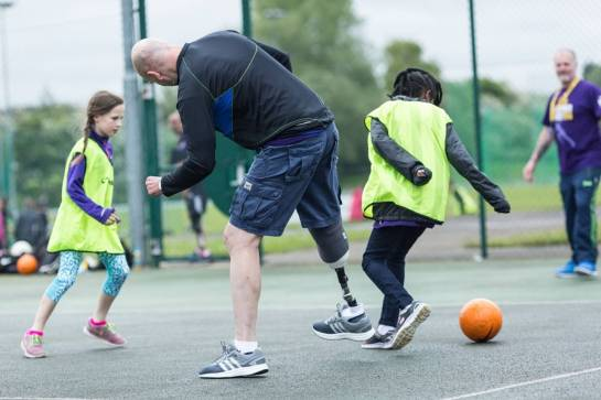 Man, who is is a leg amputee, playing football with children