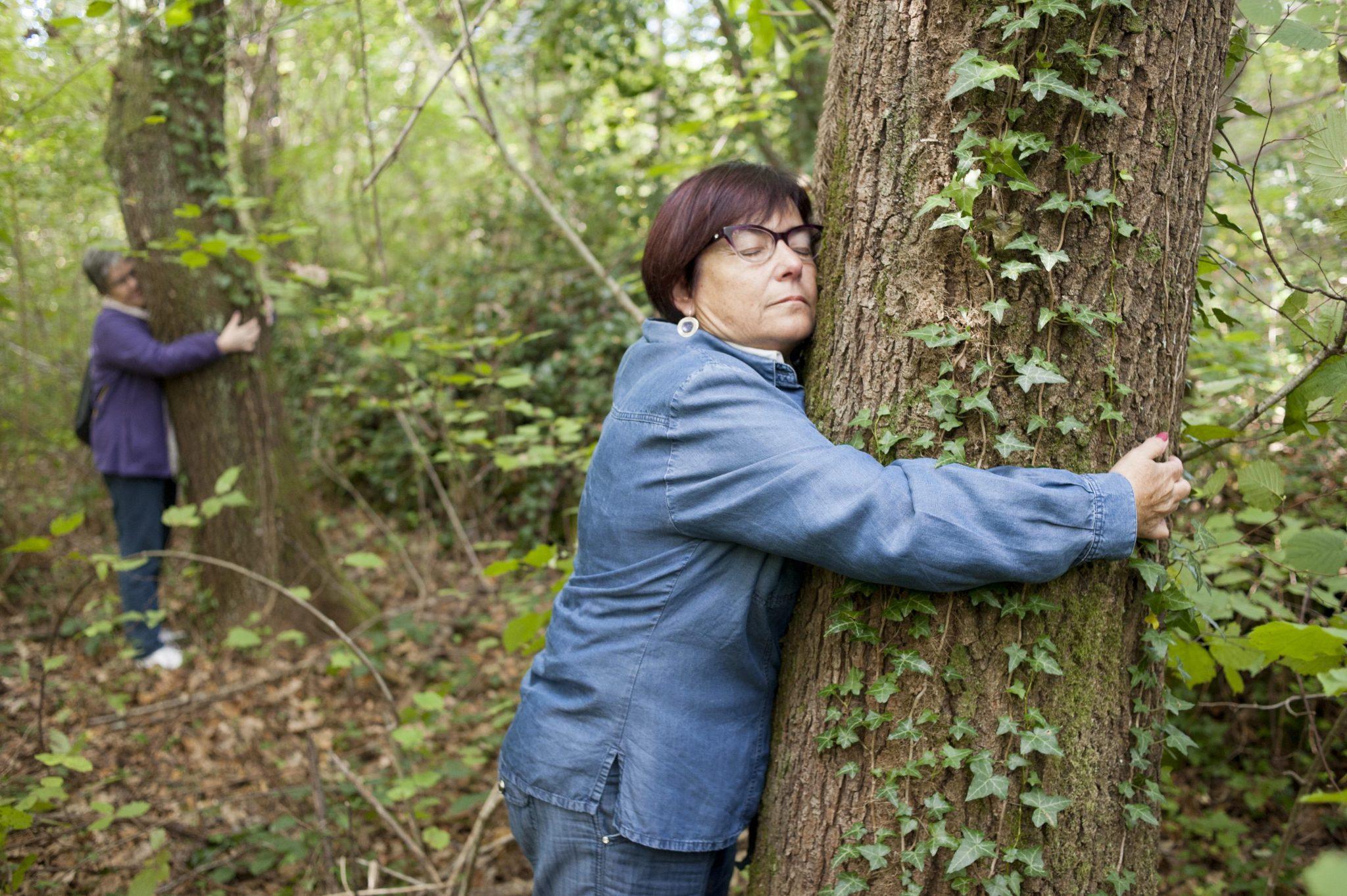 Dos pacientes abrazan a sendos árboles en un bosque cerca de Olot como parte de una terapia contra la fibromialgia y el síndrome de fatiga crónica. EFE/Robin Townsend[
