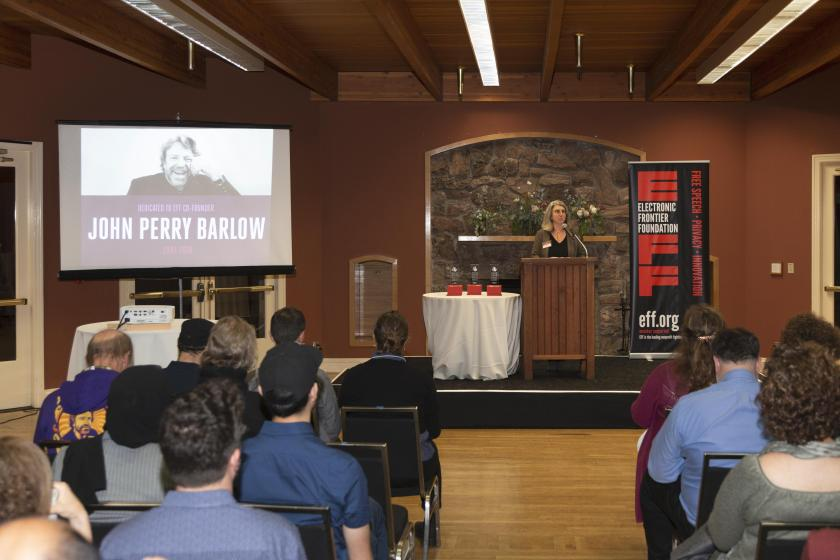 """Picture of screen and raised dias with podium. To the left, is a projected image of our co-founder, John Perry Barlow. At the poduim on the right is our Executive Director Cindy Cohn, opening the """"Barlow"""" dedication."""