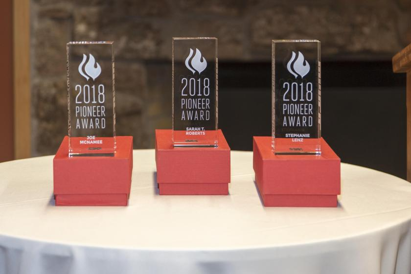 """Three 9"""" by 3"""" by 2"""" rectangular awards in clear acrylic. Front engraved with """"2018 Pioneer Award"""" and """"Joe McNamee"""", """"Sarah T. Roberts"""" and """"Stephanie Lenz"""", respectively."""