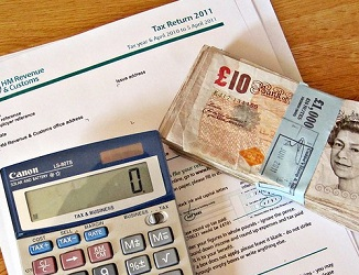 paper tax return form with a calculator and ten pound notes