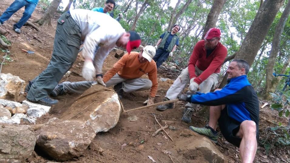 幾個人合力把石塊的「碎片」拉到斜坡上,準備埋入預先挖好的坑裏。