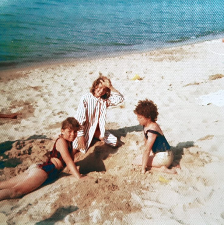 Three white children playing on the beach, lake in the background