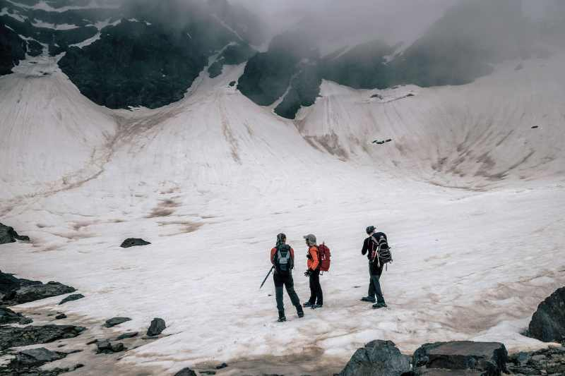 Three climbers observing a mountain.