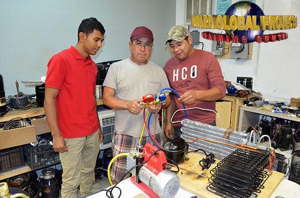 De izquierda a derecha-Santy Suáres, Benito. Jaramillo y Leonel Hernández - Carga refrigerante, a un módulo de refrigeración