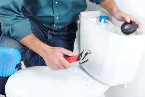 Plumber fixing a toilet