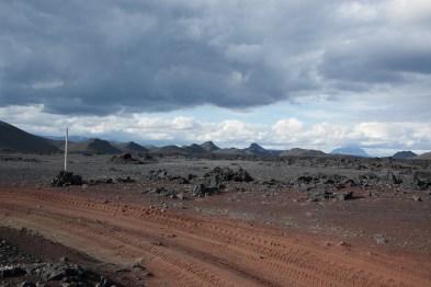 Schotterpiste, Lavasand und -felsen, graue und weiße Wolken...