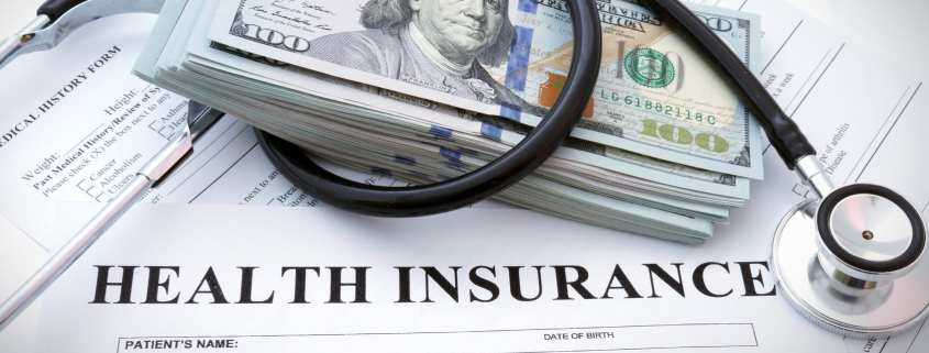 Health insurance form with dollars and stethoscope