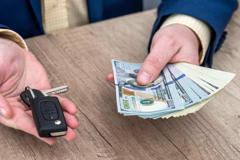 Businessman holding car key and money
