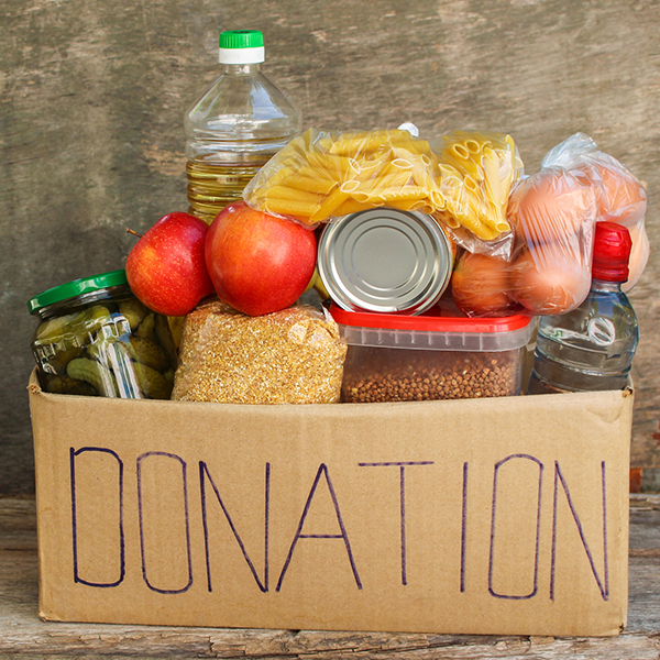 Cardboard box with the word donation written on it, filled with food