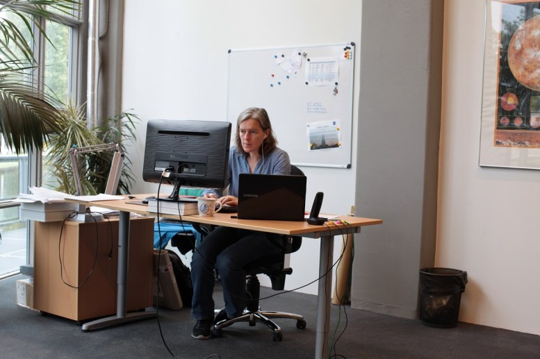 Maria at her desk, with headphones.
