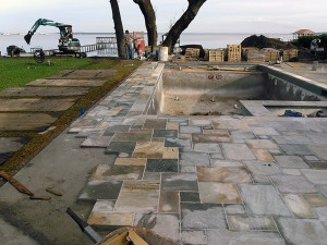 Natural slat stone masonry Cut natural slat stone in a French pattern for pool decking.