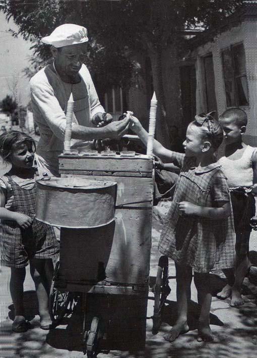 Στην φωτογραφία απεικονίζεται ένα παγωτατζής μς άσπρο σκούφο - καπέλο, άσπρα ρουχα και γύρω του είναι μαζεμένα παιδακια που τους δίνει παγωτό