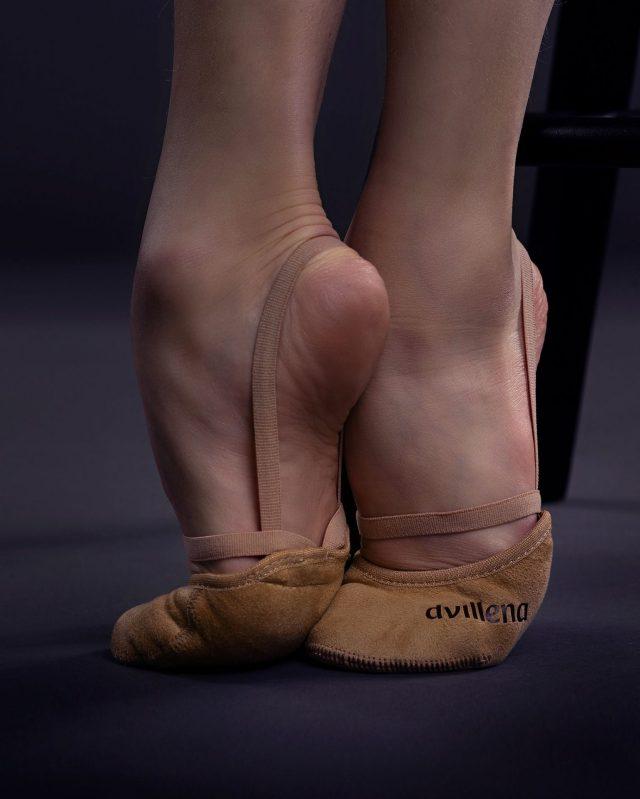 Dvillenan Sensación puolitossut korkealla päkiällä seisovan rytmisen voimistelijan jalassa.