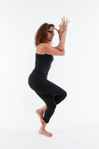 Girl practicing yoga, eagle posture on white background