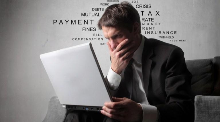 hombre mira computadora preocupado por multa