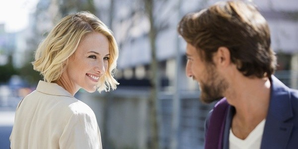 man staring at woman smiling