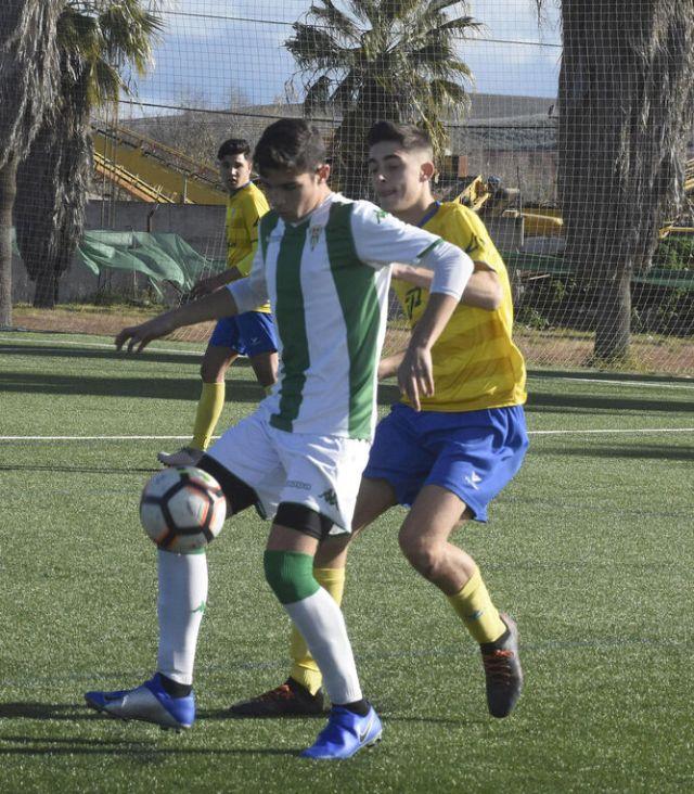 Un jugador del Córdoba protege el balón ante un jugador del Tomares.
