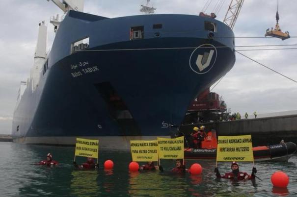 Varios activistas de Greenpace soportan varias pancartas frente al carguero saudí en señal de protesta.
