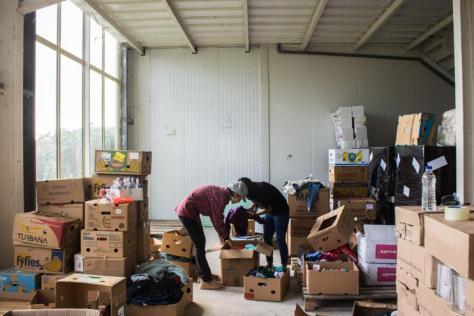 Dos voluntarias refugiadas colaboran en el almacén de Attika