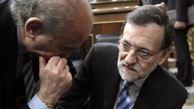 El presidente del Gobierno, Mariano Rajoy (d) y el ministro de Interior, Jorge Fernández Díaz.