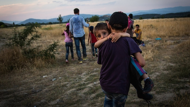 A young Syrian refugee carries his brother across the border between Greece and Macedonia, near Eidomeni, Greece.