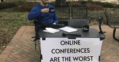 "A man sits behind a sign that says ""Online Conferences are the worst - Change My Mind"""