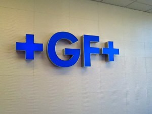 Picture of blue dimensional letters on white tile wall.