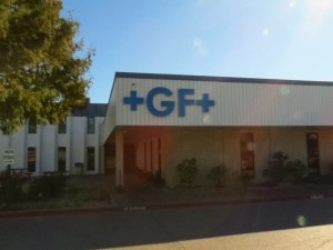 Picture of +GF+ blue channel letters mounted to side of building overhang.