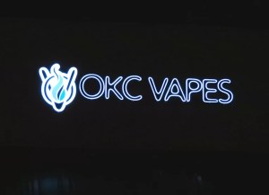 Nighttime picture of illuminated channel letter sign for OKC Vapes in Norman, OK.